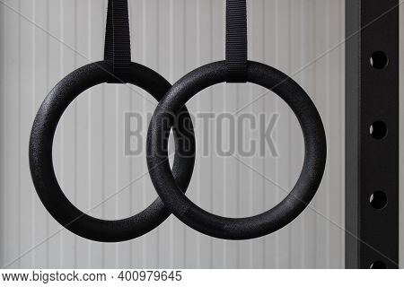 Close-up Of Set Of Black Gymnastic Rings Or Steady Rings Hanging In Steel Power Rack Over A White Wa