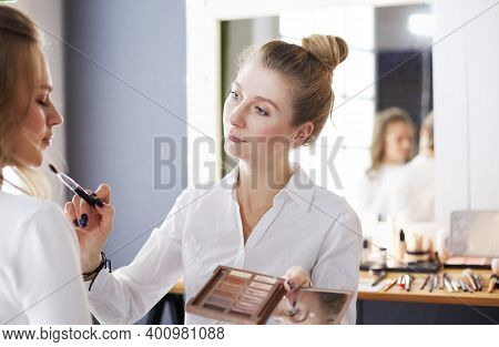 Make-up Artist Applying White Eyeshadow In The Corner Of Models Eye And Holding A Shell With Eyeshad