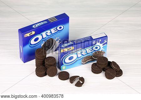 Oreo Sandwich Cookies And Blue Product Boxes On White Table. Oreo Is A Sandwich Cookie With A Sweet