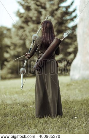Young Woman Archer In Green Medieval Costume Stands With Her Back