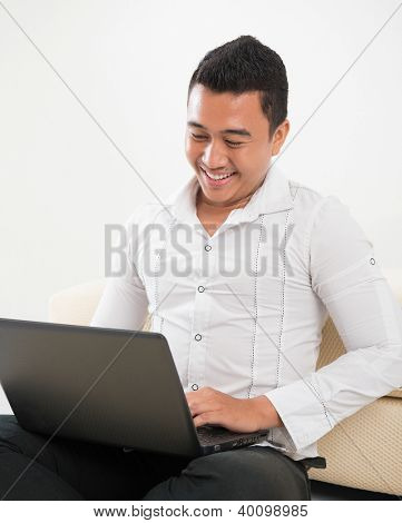 Southeast Asian man sitting on floor, browsing internet.