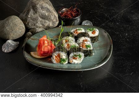 Sushi Rolls With Salmon And Chuka Salad. A Traditional Japanese Dish Of Raw Fish Fillets, Cream Chee