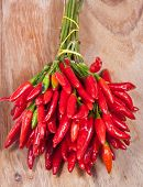 bunch of fresh small cayenne red pepper on wood table poster