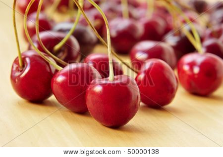 closeup of some appetizing cherries on a wooden surface