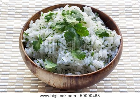 White rice with coriander or cilantro, in wooden bowl.