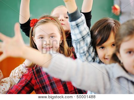 Cute lovely school group of children at clasroom having education activities