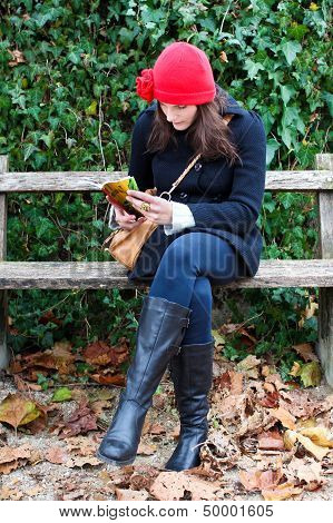 Woman Sitting On A Bench And Reading A Book