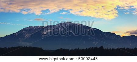 The Austrian Alps With Orange Sky And Clouds Above Them