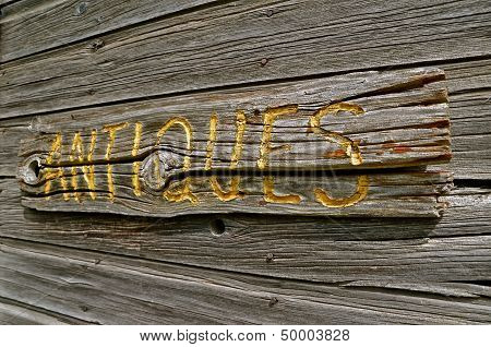 antique carved sign on weathered wood wall