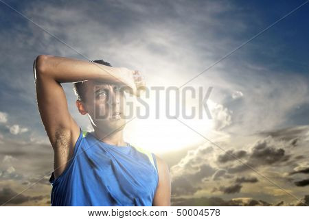 Young Athlete Shielding His Eyes from the SUn