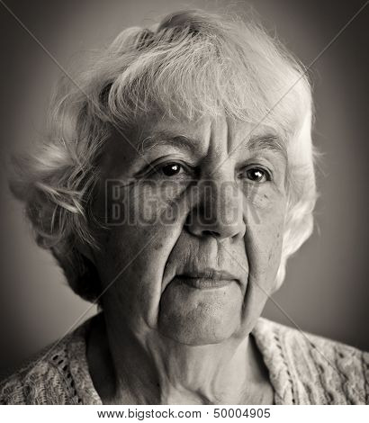 Black and white portrait of an old gray-haired woman.