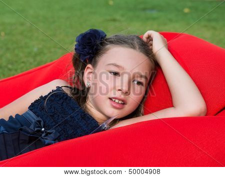 Little girl in a dark blue dress lying on the red inflatable mattress in the Park