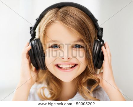 home, technology and music concept - little girl with headphones at home