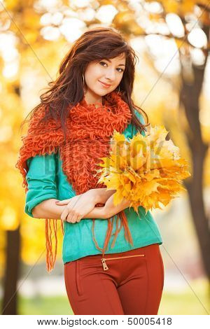 Young pretty woman walking in the autumn park