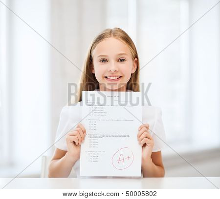 education and school concept - little student girl with test and grade at school