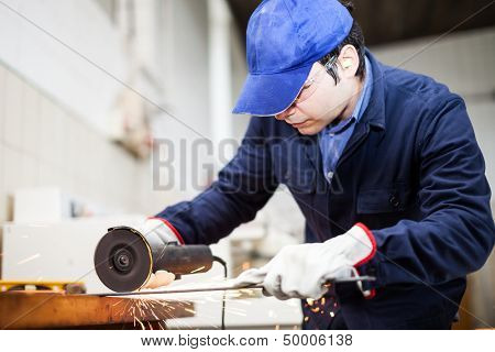 Worker using a grinder on a metal plate