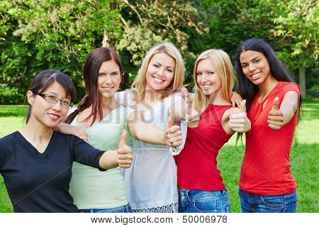 Group of young happy women in nature holding their thumbs up