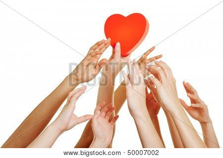 Many hands reaching for red heart as symbol for dating