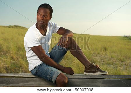 Portrait Of A Handsome Young Man Sitting Alone Outside