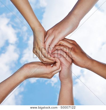 Many hands connecting for help in a spiral under a sky