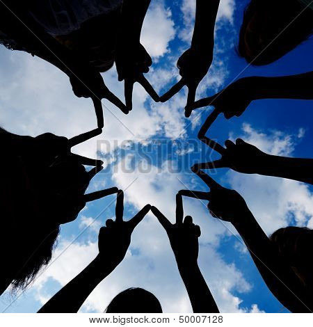 Silhouette of many hands forming star network under a sky