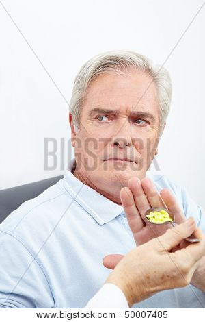 Senior patient refusing to take medicine on a spoon