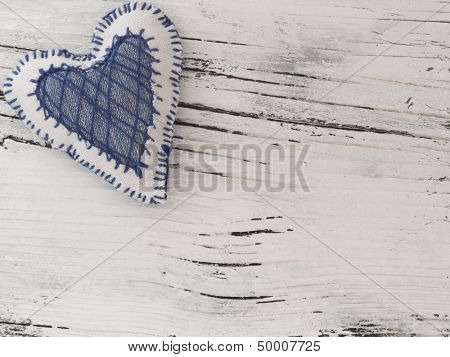 textile heart on the white wooden background