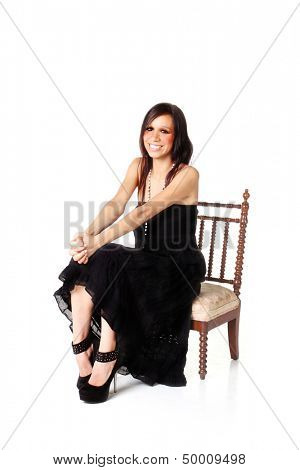 Native American Woman in black dress seats on a little chair