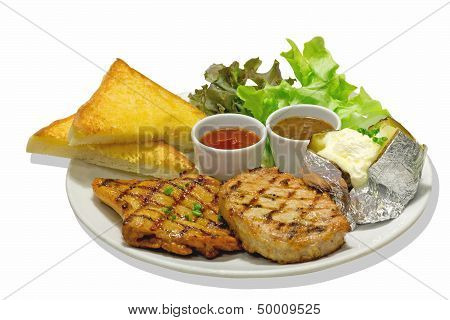 pork and chicken steak on a white plate