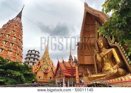 Wat tham khao noi buddhist temple under a cloudy sky in rainy season, Kanchanaburi province in Thaialnd
