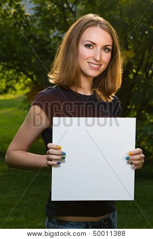 Happy Smiling Young Girl Holding White Blank Paper Against Background Of Summer Green Park