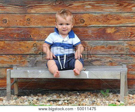 Little boy sitting on the rural bench.