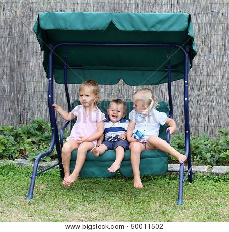 Funny kids playing on a garden swing.