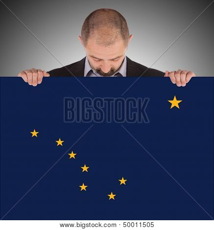 Smiling Businessman Holding A Big Card, Flag Of Alaska