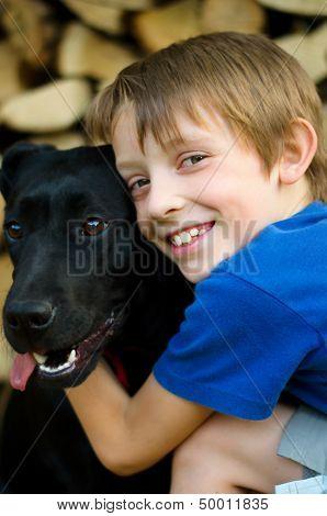 Boy Hugging Black Dog