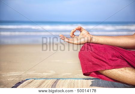 Meditation mudra of man in red trousers on the beach at ocean background poster