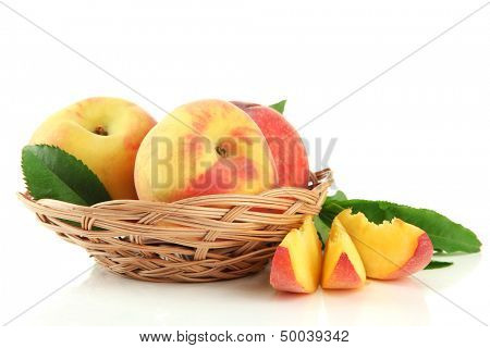Ripe sweet peaches with leaves in basket, isolated on white