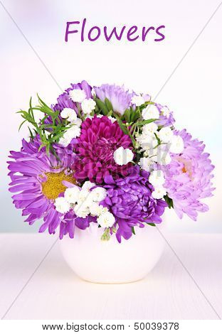 Beautiful bouquet of bright flowers in vase on bright background