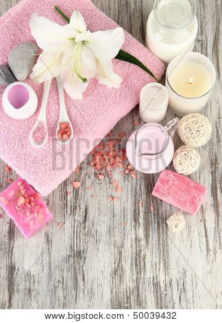 Beautiful spa setting with lily on wooden table close-up