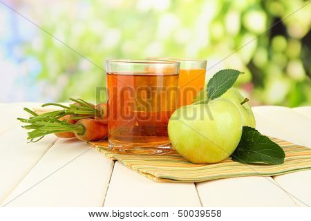 Glasses of juice, apples and carrots on white wooden table, on green background