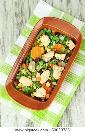 Casserole with vegetables and meat, on wooden background