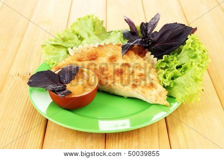 Tasty chebureks with fresh herbs on plate,on wooden background