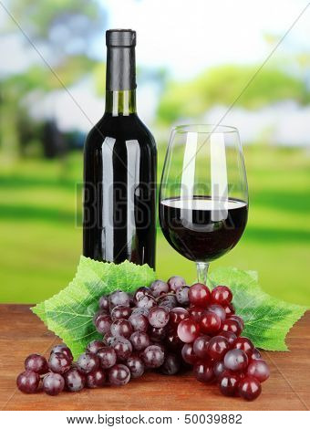 Ripe grapes, bottle and glass of wine on bright background