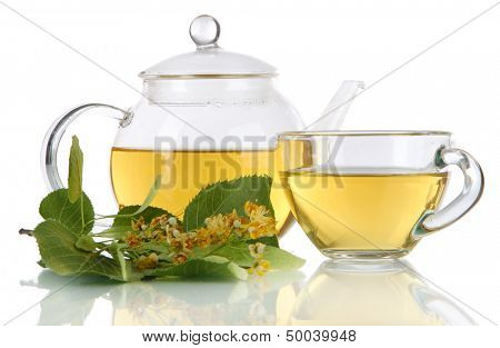 Kettle and cup of tea with linden on  wooden table nature background
