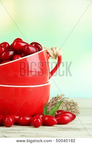 Fresh cornel berries in red cups on wooden table