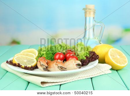 Boiled crab claws on white plate with salad leaves and tomatoes,on wooden table, on bright  background