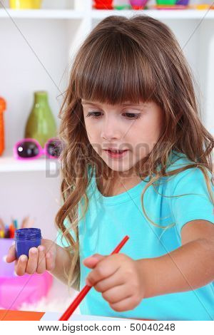 Little girl draws sitting at table in room on shelves background