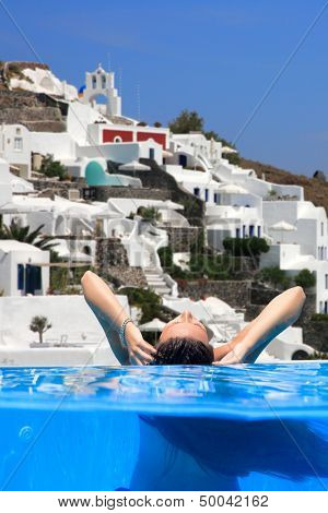 Over Underwater Young woman enjoying the view of Santorini island Greece
