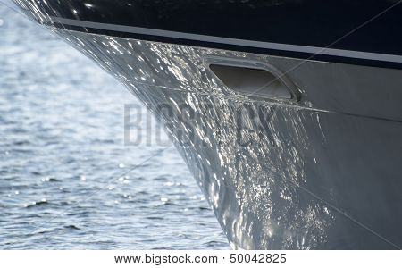 Hull Of Yacht Sailboat With Sea Reflections