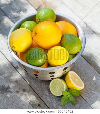 Fresh ripe citruses in colander on wood table